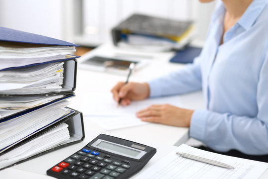 Calculator and binders with papers are waiting to be processed by business woman or bookkeeper back in blur. Internal Audit and tax concept