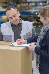 Woman signing to receive delivery in warehouse