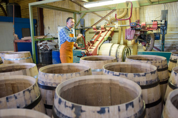 Cooper in background of barrel making factory