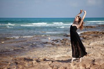 Young attractive ballerina training on sea coast wearing long black dress. Fine art ballet concept. Surreal dancing. Slim girl dance on the ocean beach. Active and healthy women