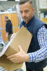man carrying cardbox at warehouse