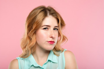 emotion expression. suspicious thoughtful dubious woman with a distrustful look. young beautiful blond girl portrait on pink background.