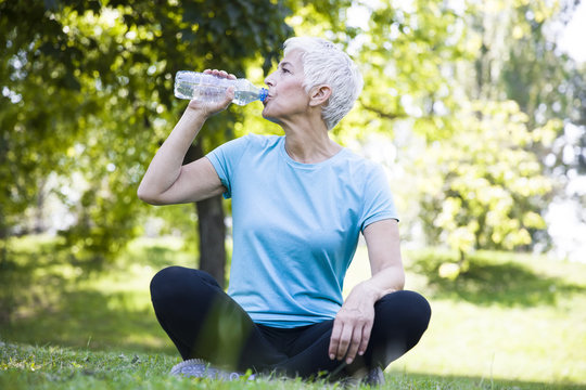 Senior woman resing and drinking water after workout in park
