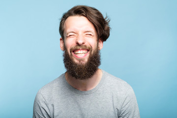happiness enjoyment and laugh. exhilarated man with a wide grin. portrait of a young bearded hipster guy on blue background. emotion facial expression. feelings and people reaction. Wall mural