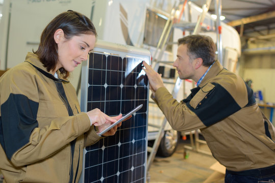 campervan factory employees checking solar panels on van