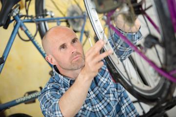 handyman fixing bike wheel in his garage