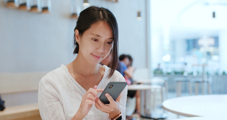 Woman check on cellphone in cafe