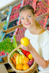 Woman holding a basket full of different fruit