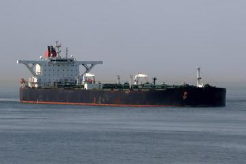 schwarzer Supertanker läuft in Hafen ein