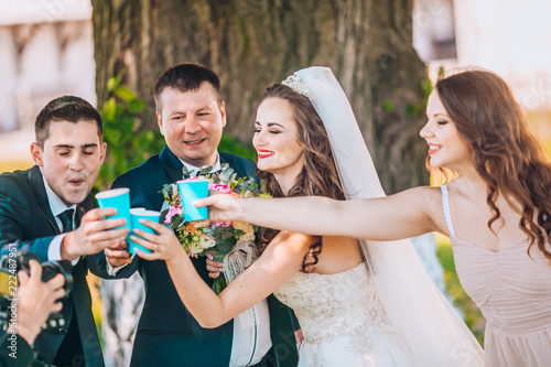 Newlyweds And Their Friends Open Champagne Bottle Standing In The Park Before Wedding Ceremony