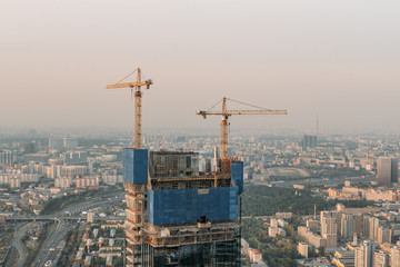 Two cranes near high building. Skyscraper under construction on city background, aerial view