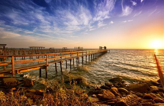 Long wooden docks reach into Galveston Bay, Texas, at sunrise