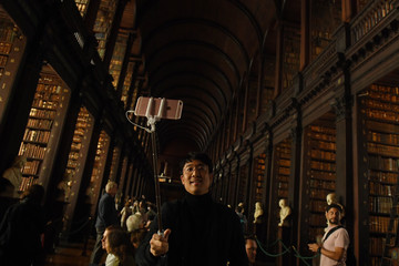 A tourist uses a selfie stick to take a picture in the Long Room of the old library that houses 200,000 of Trinity College's oldest books in Dublin