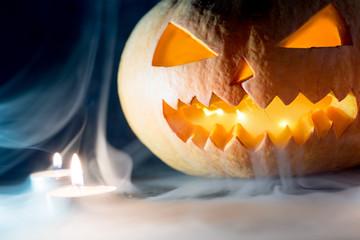 Orange crazy pumpkin lantern looks through the smoke. Dark background with candles