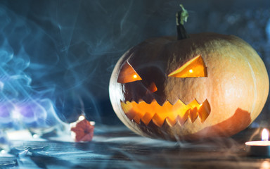 Cool pumpkin killer on Halloween in smoke on dark background with candles