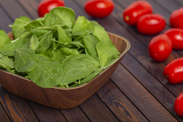 Tomatoes and spinach leaves on wooden table