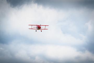 Vintage red propeller plane flying on a blue sky