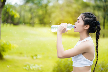 Asia woman drinking good quality water After the exercise of sweat. Which made her feel refreshed. And bright again Water is good for health and makes the body healthy.
