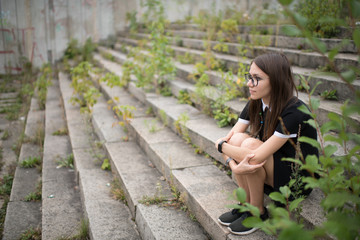Lonely young woman sitting on overgrown stairs