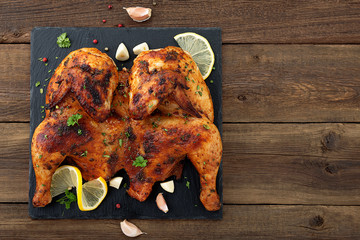 Grilled fried roast Chicken Tabaka on  wooden background. top view