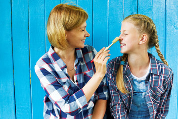 Mom smears a nose with a paint brush to the child. Repairs. Time Together