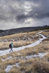 Hiker on trail across Mt Etna, Sicily, Italy