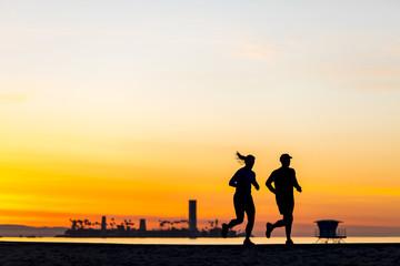 Man and woman jogging at sunrise