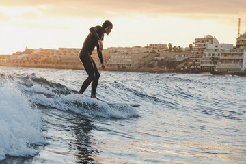 Surfer in sea at sunset
