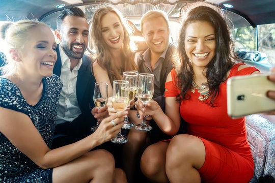 Party Männer und Frauen in einer Limo machen ein Handy Selfie