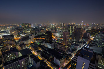 Scenic view of many lit skyscrapers and other buildings in downtown Bangkok, Thailand, from above at night.
