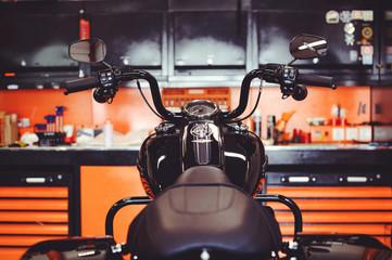Foto op Plexiglas Fiets motorcycles on the floor with workshop tools, a modern garage, storage and repair. This bike will be perfect. repairing a motorcycle in a repair shop