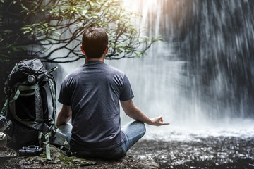 Yoga of traveler relaxing in front of waterfall with backpack and travel equipment. Travel lifestyle concept