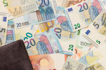 Money background. Brown wallet lies on a panel of euro banknotes of various denominations