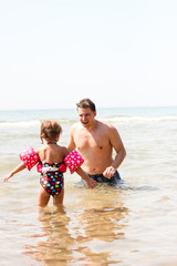 A father playing with his daughter in sea