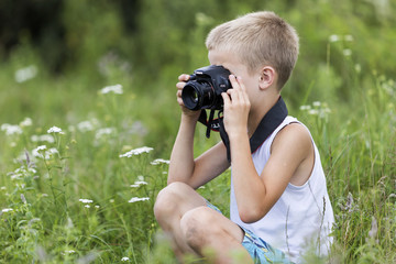 Profile close-up portrait of young blond cute handsome child boy with camera taking pictures outdoors on bright sunny spring or summer day on blurred light green grassy copy space background.
