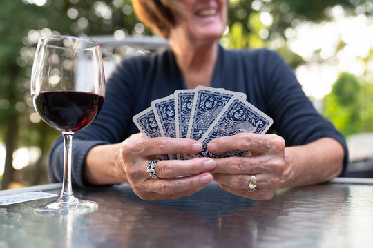 Close up of a senior woman holding playing cards