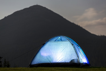 Summer camping at night. Illuminated tourist tent on green clearing on distant mountain background.