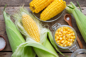 Canned sweet corn in glass jar, fresh and cooked corn on cobs, salt. Top view.