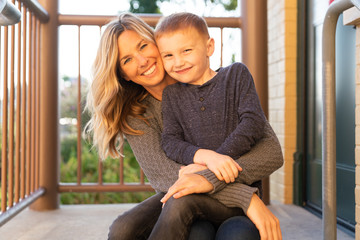Portrait of smiling mother and son sitting on balcony