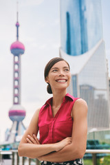 Business in China - chinese businesswoman confident looking at Shanghai skyline in Pudong financial district. Young professional Asian multiracial woman smiling. Businesspeople lifestyle portrait.