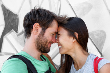 Interracial couple young happy Asian woman and Caucasian man lovers smiling laughing kissing portrait. Tourists on travel holiday taking phone selfie picture hugging each other.