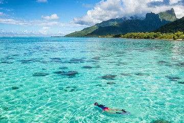Photo sur Plexiglas Plongée Luxury travel vacation tourist woman snorkeling in Tahiti ocean, Moorea island, French Polynesia. Snorkel swim girl swimming in crystalline waters and coral reefs.