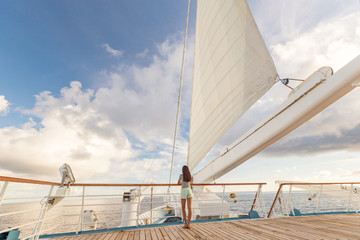 Luxury cruise ship vacation woman relaxing on deck at sunset Travel in Tahiti on sail boat, exotic destination. Tourism in oceania. Boat sailing away on tropical getaway traveling in French Polynesia.