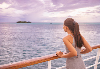 Luxury cruise vacation woman looking at exotic Tahiti landscape from boat deck at sunset. Elegant tourist young girl relaxing at view of ocean scenery outdoor. Sailing lifestyle holidays.