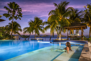 young woman in a luxury pool enjoying the beatiful sunset on the beach in bali