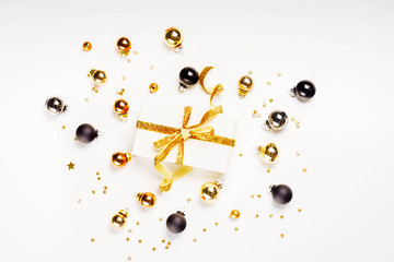 Christmas flat lay scene with golden, gray and black glass balls and gift box with golden bow, retro toned