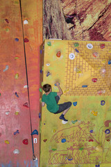 The boy clambers up on the rock climbing wall