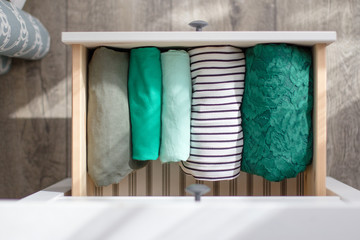The clothes of green tones are neatly folded in the chest of drawers