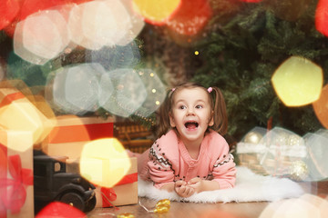 Little girl in new year's Christmas atmosphere. The girl is happ