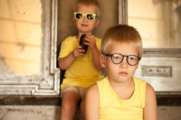 Two children in yellow T-shirts and glasses with occluder play against background of old mirror. Ortopad Boys Eye Patches. Boys are happy together. Nozzle for glasses to treat strabismus (lazy eye)